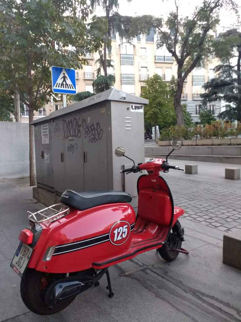 A red scooter with a black stripe and number 125.