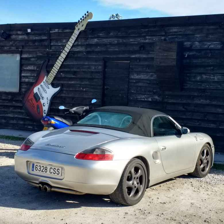 A silver, early 2000s Porsche Boxster next to a blue motorbike and a red and white electric guitar.