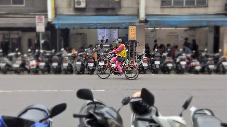 Man in pink pedaling a pink tricycle among a sea of motorbikes in Taipei, Taiwan. (May 1, 2016)