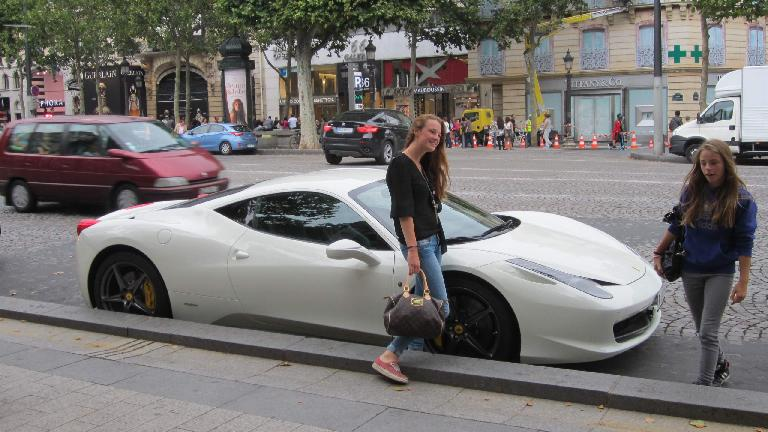 A young lady posing with a Ferrari 458 Italia off the Champs-Elys̩es in Paris.