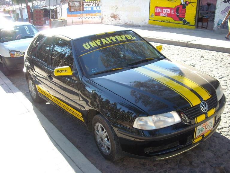 "A custom Volkswagen sub-compact with ""infiel"" and ""unfaithful"" decals."