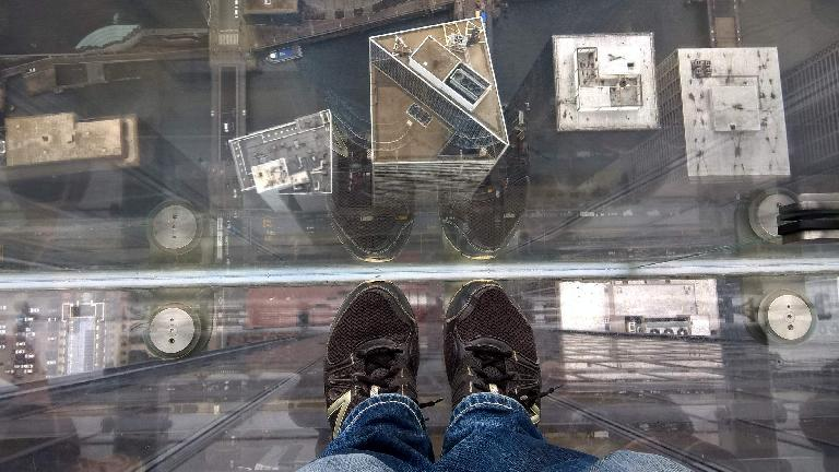 black shoes, looking down at buildings, on top of buildings, clear glass