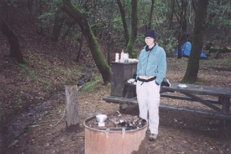 """Warming up some """"hot vanilla"""" in the morning.  Unfortunately the camera lens focused on our tent in the background instead of the intended subject. (December 24, 2001)"""