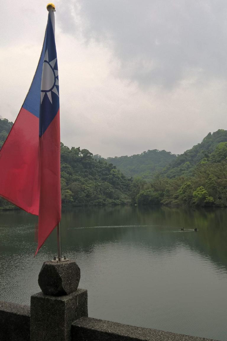 Taiwanese flag and ducks on a lake near the Cihu Mausoleum.