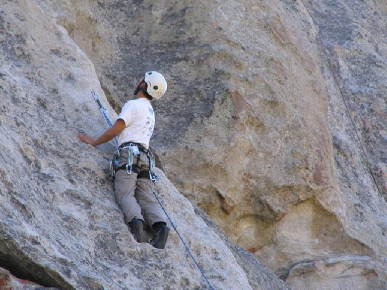 Felix Wong scanning the rock above and pondering his next move after clipping a bolt. Photo: Tori.