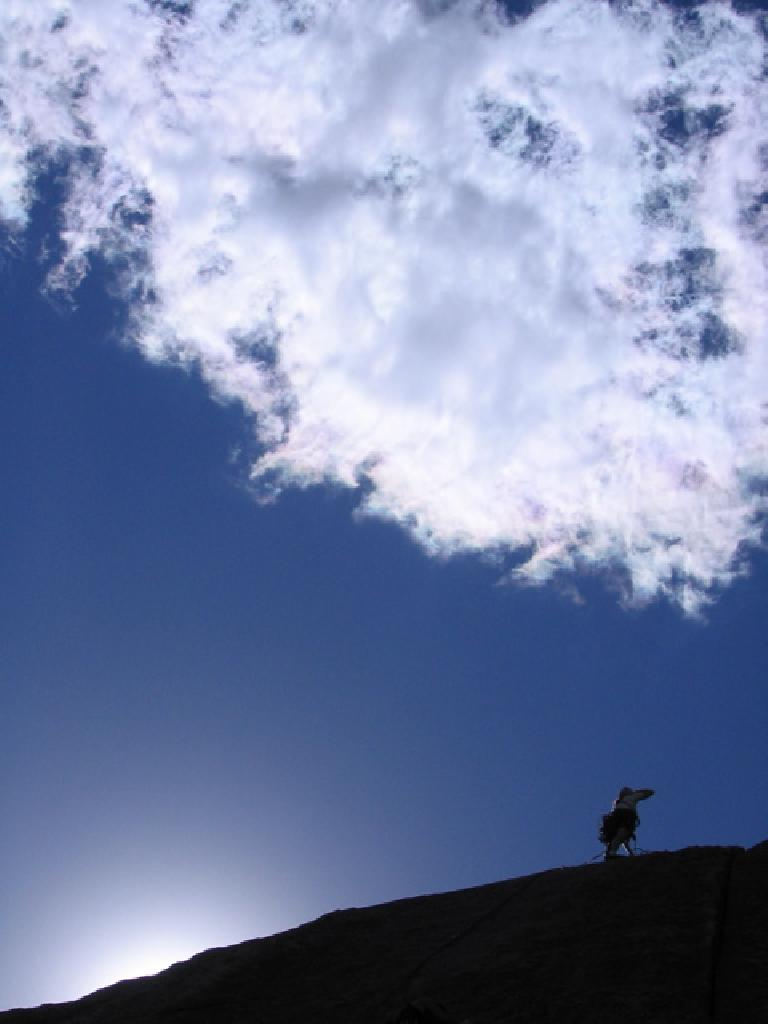 Tori reaches the top as a puffy white cloud looms overhead.