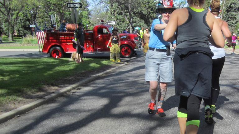Red firetruck, firewoman, shirtless fireman