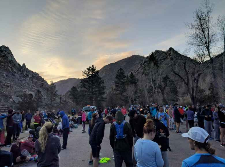 Runners in the starting area of the 2019 Colorado Marathon, with the sun starting to rise about the mountains of the Poudre Canyon.