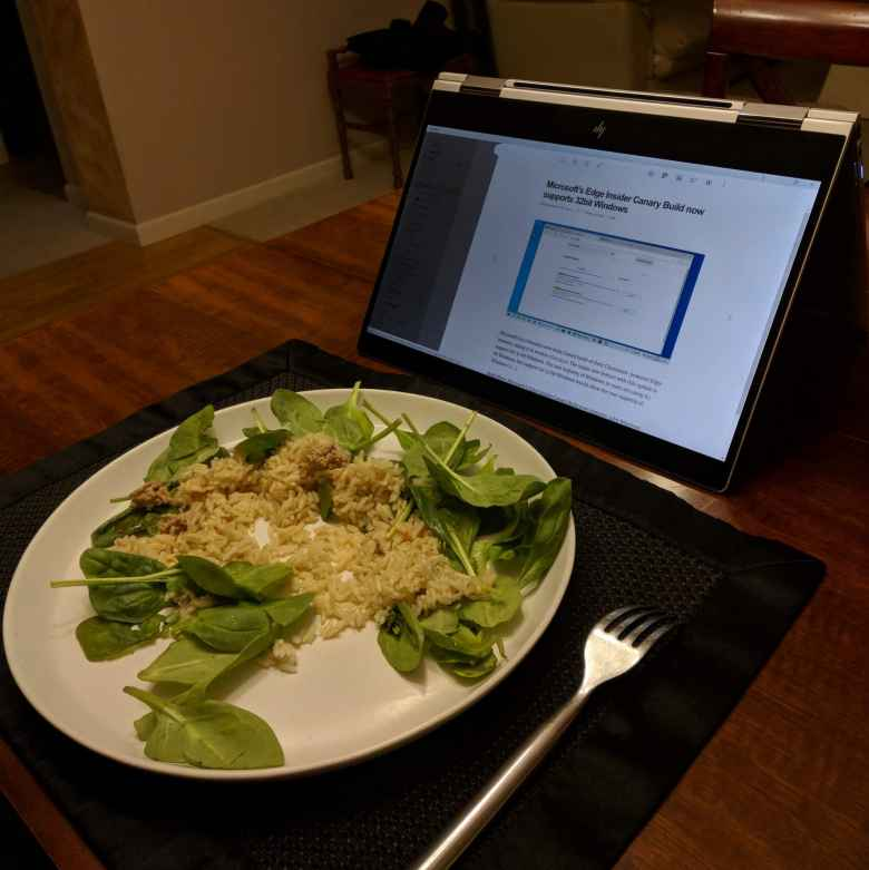 silver HP Spectre x360, tent mode, white plate with rice and spinach