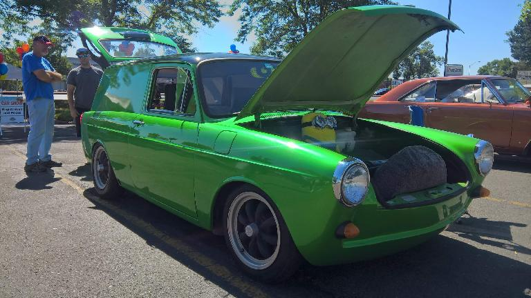 A custom green Volkswagen two-door wagon with a minion inside the front trunk.