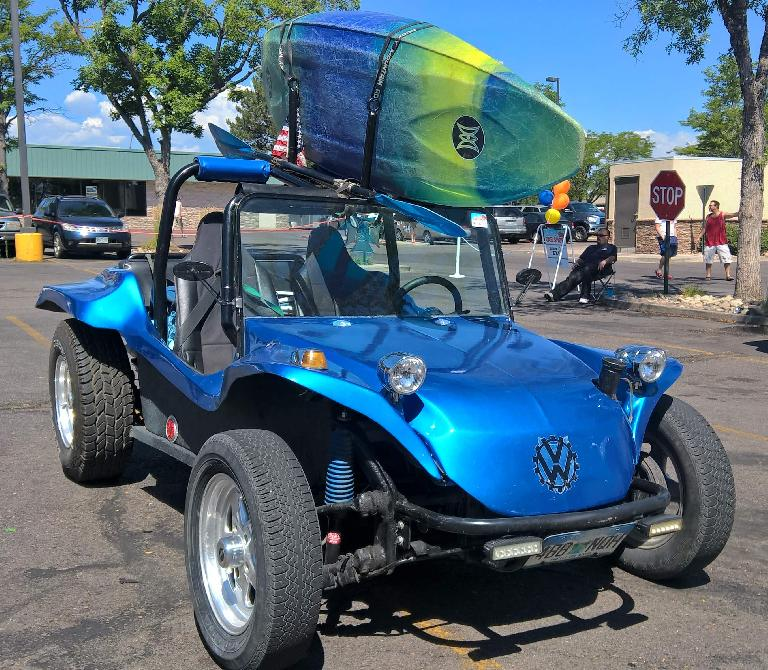 A blue Volkswagen dune buggy with a surfboard on top.