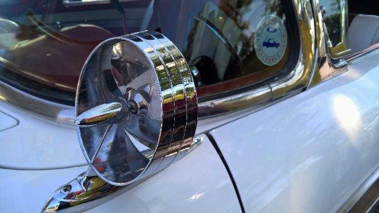 Mirror detail of a white Ford Fairlane hardtop convertible.