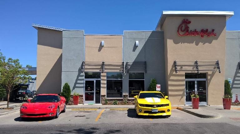 A red C6 Corvette and yellow Chevrolet Camaro (not part of the show( in front of Chik-fil-A in Fort Collins.