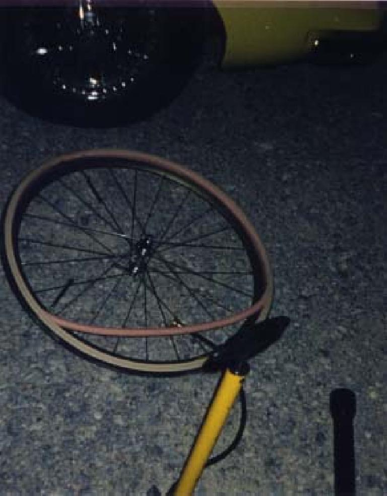 bicycle wheel on the ground with tire and tube off and a yellow bicycle pump at night