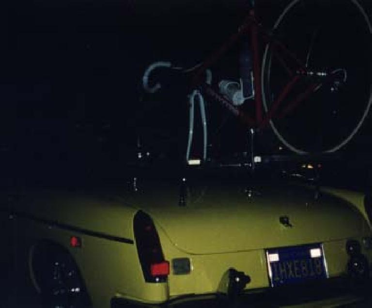 red bicycle mounted on top of yellow MGB roadster at night.