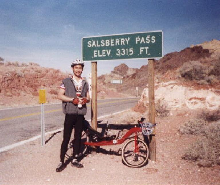 Felix Wong and his red Reynolds Wishbone recumbent, Salsberry Pass sign, elevation 3315 ft., 2000 Death Valley Double Century