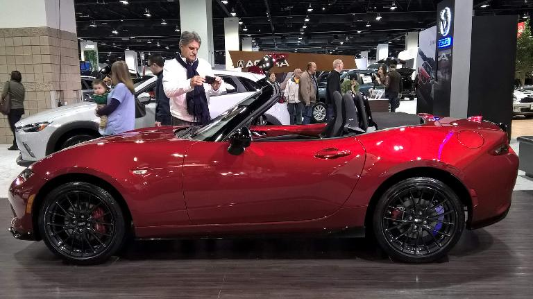 Red 2016 Mazda MX-5/Miata with the top down.