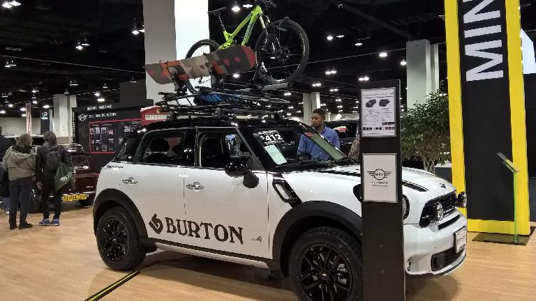 White 2016 Mini Countryman with snowboard and mountain bike.