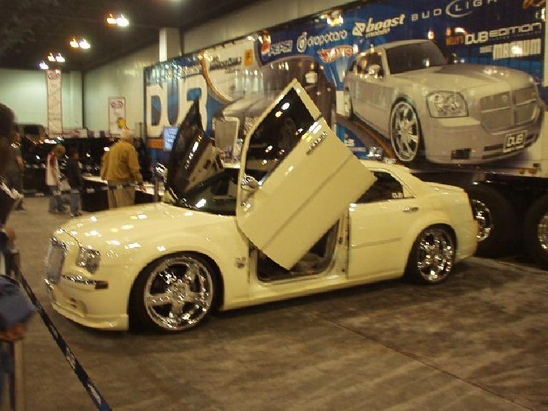 "Snoop Dogg's custom Chrysler 300C with ""Lambo doors"" and ""seats that took 7 hours to stitch by hand"" was on display.  What a waste."