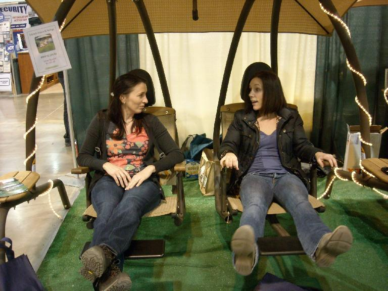 Tori and Lisa relaxing on a $4000 patio swing set.
