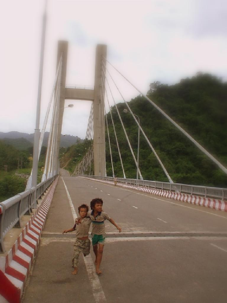 Kids on a bridge over a river.