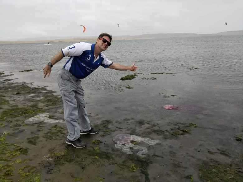 Matthew with jellyfish on the ground in paragliders in the background.