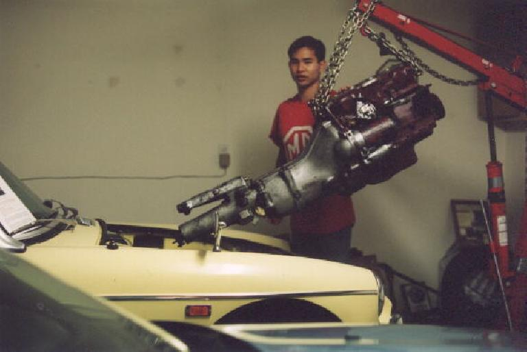 Installing the nice'n'clean engine and transmission as a unit!  It was actually quite a challenge to align everything just right and mount everything down. (May 5, 2002)