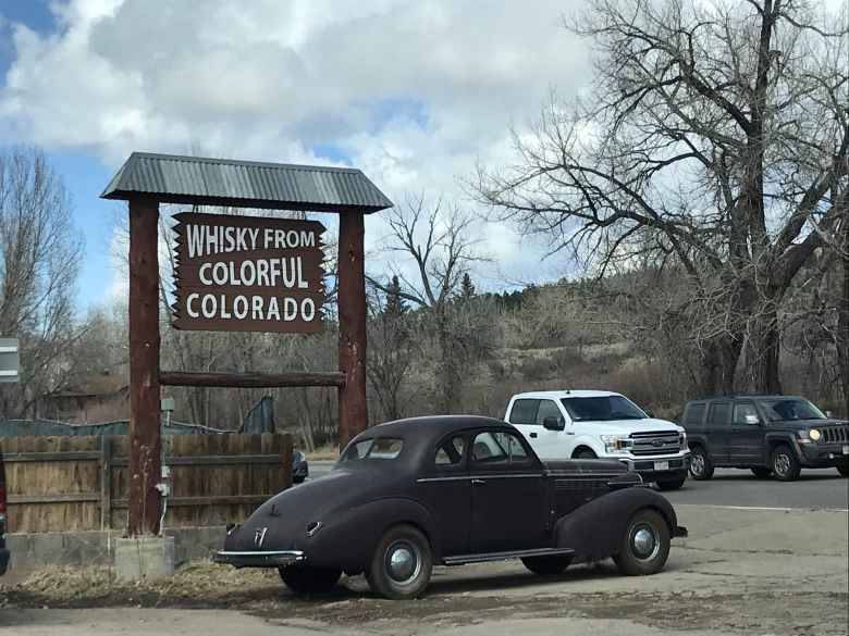 A dark deuce coupe by a Whisky from Colorful Colorado sign in Lyons, Colorado.