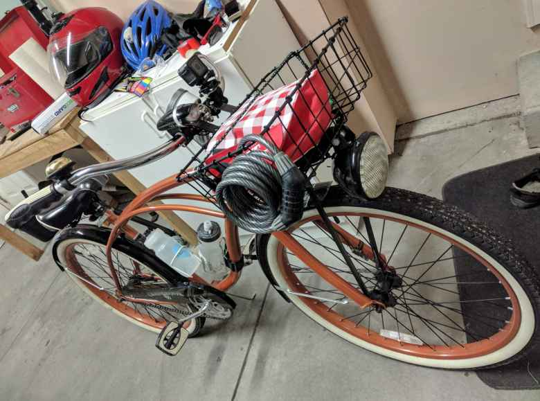 bronze Huffy Cranbrook Cruiser with basket, motorcycle light, and lock in garage