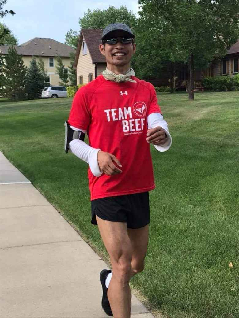 Felix Wong wearing a red Team Beef shirt, white UV sleeves, and a neck bandana for UV protection during the DIY 50 Mile run through the Hearthfire subdivision.
