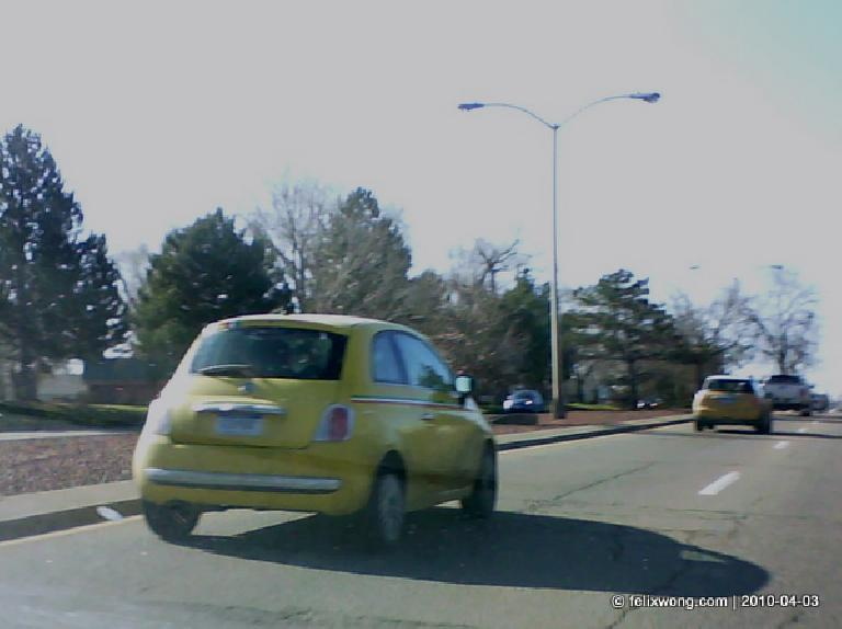A yellow FIAT 500 prototype on a road in Fort Collins.