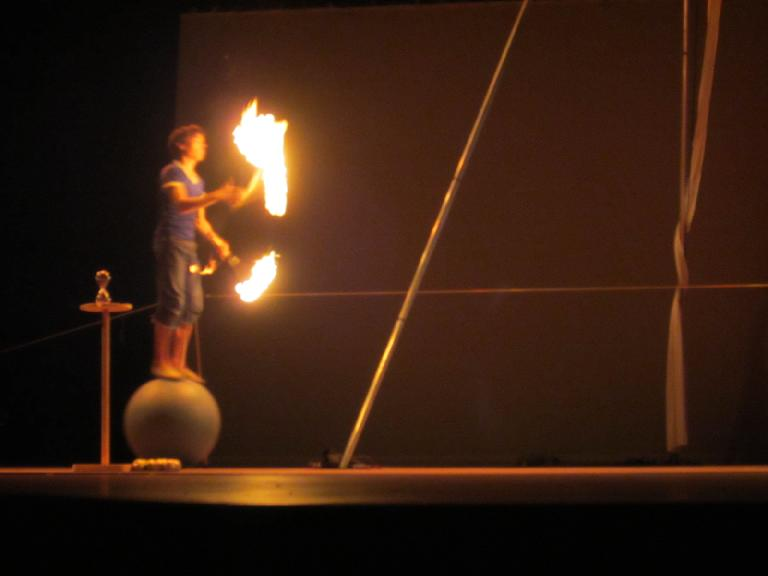 Sven Jorgensen juggling some fire sticks while rolling on top of a ball.