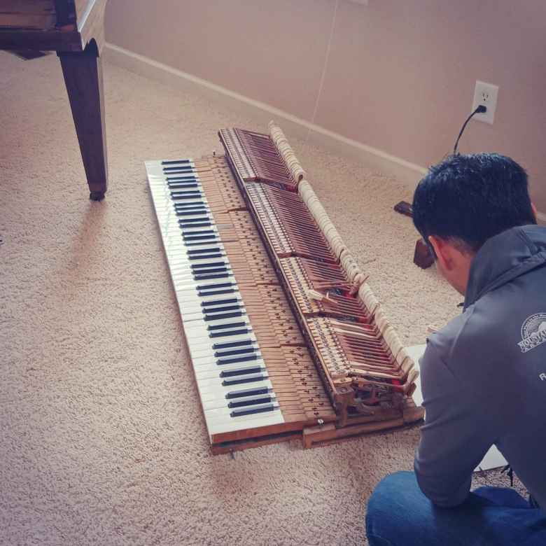 Felix Wong fixing the keyboard of a 1924 Chicago Cable Company baby grand piano.