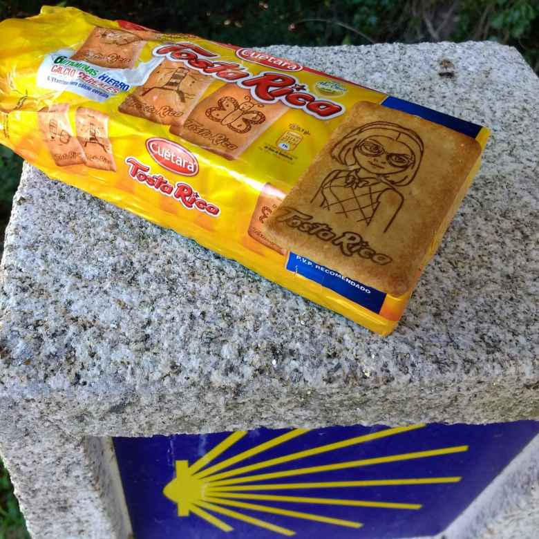 Tosta Rica biscuits with a Camino de Santiago kilometer marker.