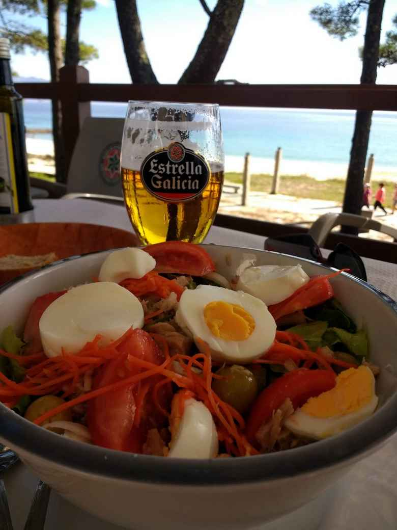 Una ensalada mixta (including eggs, tomatoes, carrots, tuna, and spinach) with a beer in Fisterra, Spain.