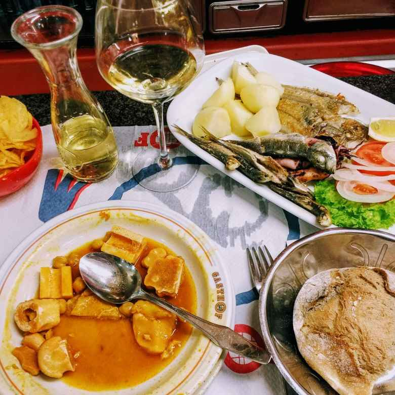 The menú del día with chips, a beef and potato stew, bread, white wine, mixed fish, potatoes, and some vegetables. It also came with dessert (not shown), for which I selected Tarta de Santiago (kind of a yellow cake).  All this cost less than 10 euros.