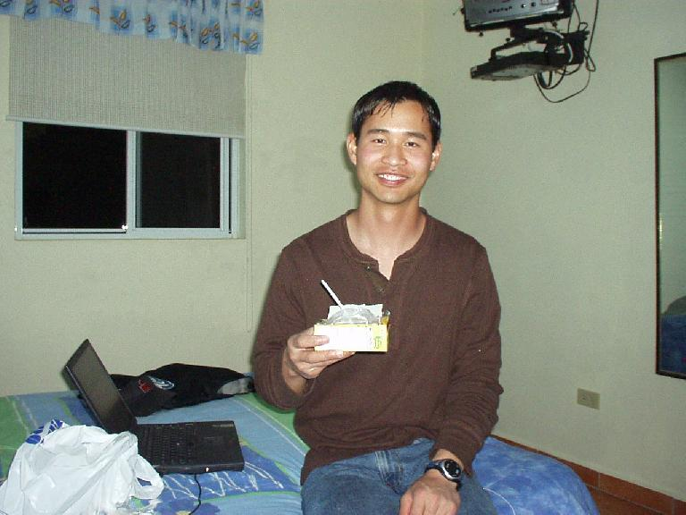 Felix Wong eating cereal out of the box for the first time using no-refrigeration-needed ultra-pasteurized milk.  He may look stoned but really was not despite taking a few puffs of a Hooka Pipe earlier in the evening. (March 6, 2007)