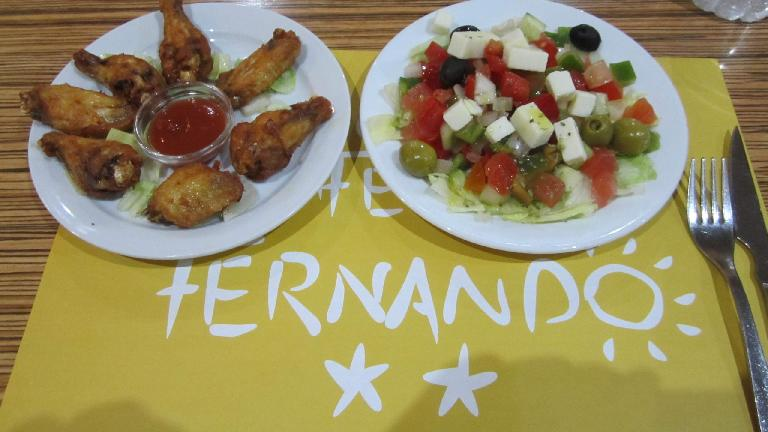 Chicken wings and Greek salad tapas at Caf? Fernando in Barcelona.