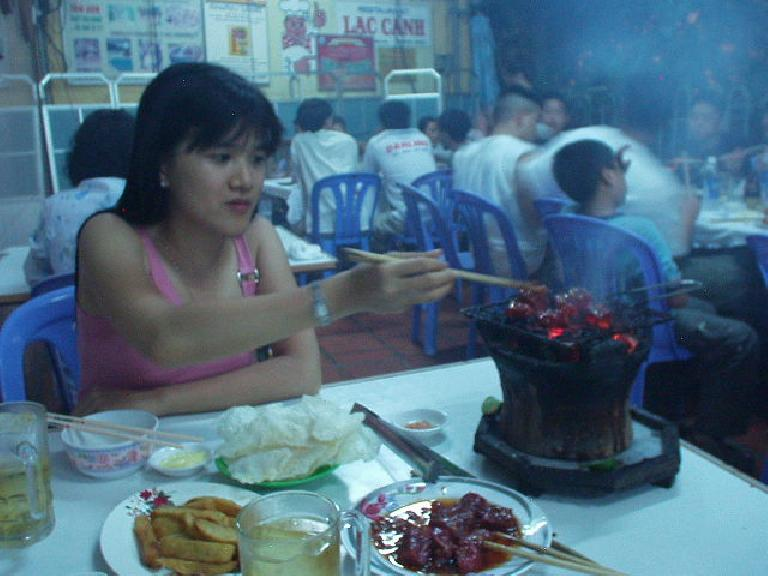 "At Lac Cahn in Nha Trang -- ""the most famous restaurant in Vietnam for beef"" -- Kristy puts more beef on the table BBQ. (July 15, 2006)"
