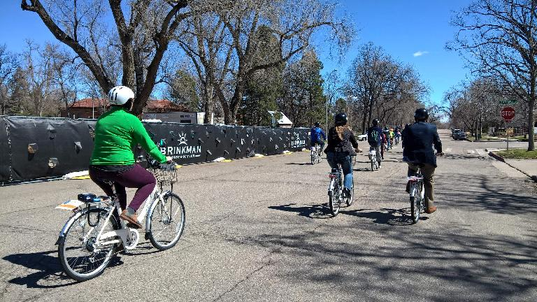 woman in green jersey riding white Zagster bicycle, other cyclists