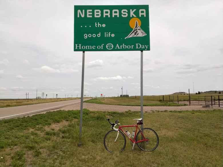 "My red 1992 Cannondale 3.0 with the Nebraska state border sign. The irony of the slogan ""Home of Arbor Day"" was not lost on me in this particular area where there was not a single tree nor bush."