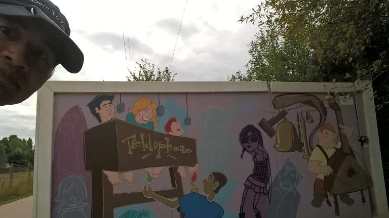 """Felix Wong and a """"Telephone"""" mural along the Power Trail in Fort Collins."""