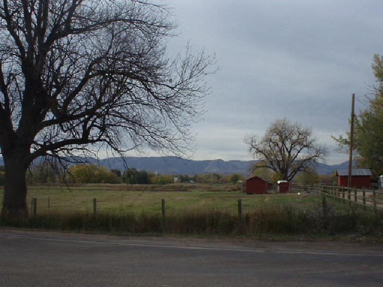 Red barns in front of the Front Range.