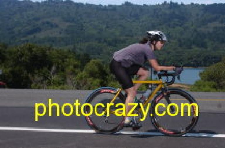 [Mile 52, 11:17 a.m.] Pretty Peggy flying by the Crystal Springs Reservoir on her time trial bike. Photo: photocrazy.com.