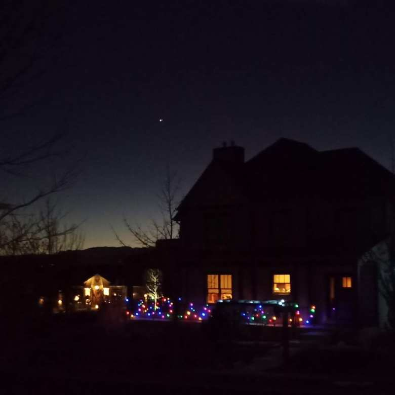 Great Conjunction of Jupiter and Saturn over two-story house decorated with Christmas lights