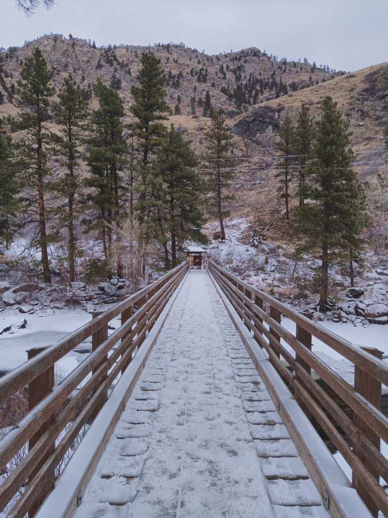 wooden bridge with snow, over the frozen Poudre River, leading to the Greyrock Trail