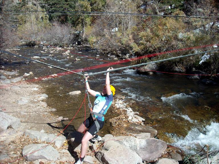 Kelly zip-lining across a creek.
