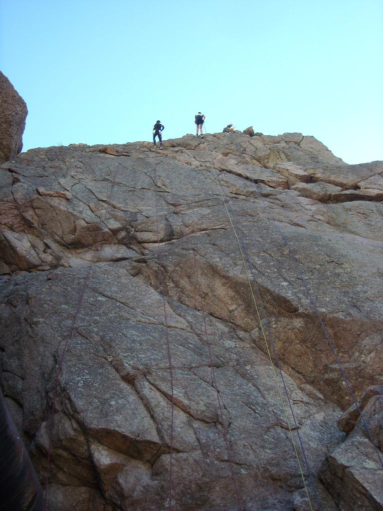 Jen and Kelly rappelling down a 120-foot cliff.