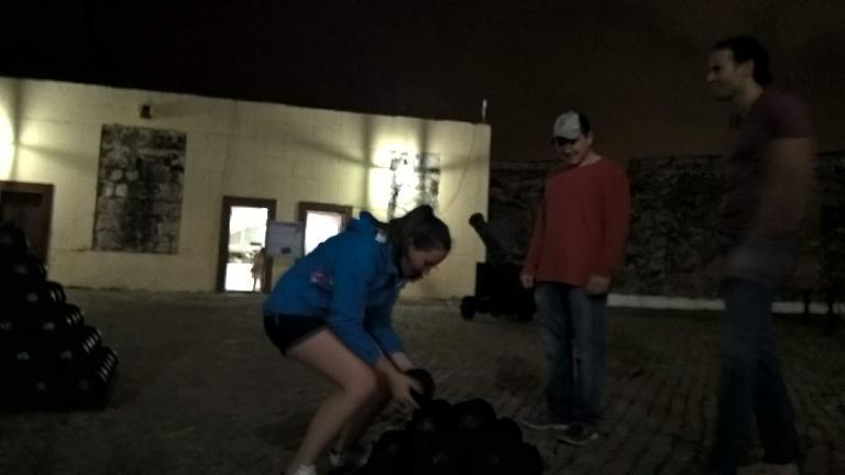 Maureen trying to pick up a cannonball at Fortaleza de San Marcos de la Cabaña.