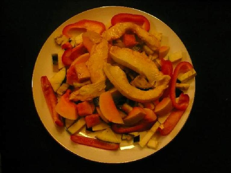 A stir fry of red bell peppers, eggplant, butternut squash, and chicken.